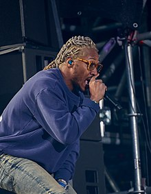 A black man with a blue sweater, Orange glasses, and bleached dreadlocks singing into a microphone