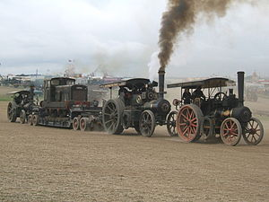 Great Dorset Steam Fair - Typical sight in the heavy haulage arena, three road locomotives combining efforts to haul a trailer, carrying a small diesel shunter, around the arena (2007).
