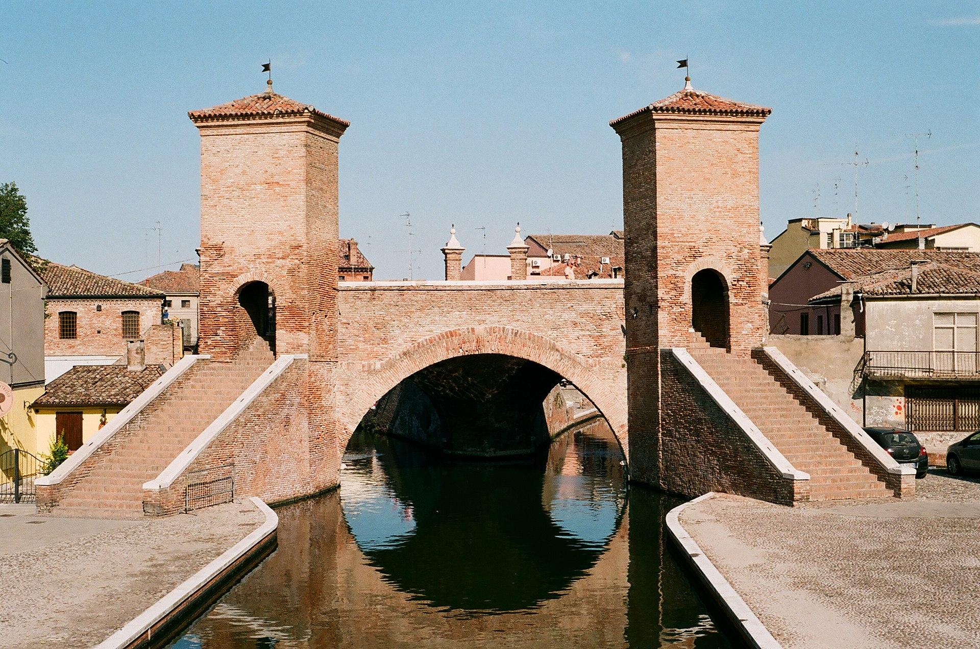 https://upload.wikimedia.org/wikipedia/commons/thumb/6/6e/Gate_to_Comacchio.jpg/1920px-Gate_to_Comacchio.jpg