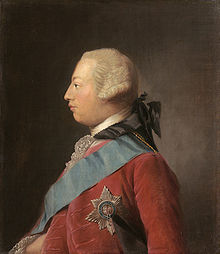 Quarter-length portrait in oils of a clean-shaven young man in profile wearing a red suit, the Garter star, a blue sash, and a powdered wig. He has a receding chin and his forehead slopes away from the bridge of his nose making his head look round in shape.