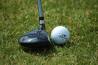 A wood positioned ready to be swung and to strike a golf ball Golf ball resting near fairway wood.jpg