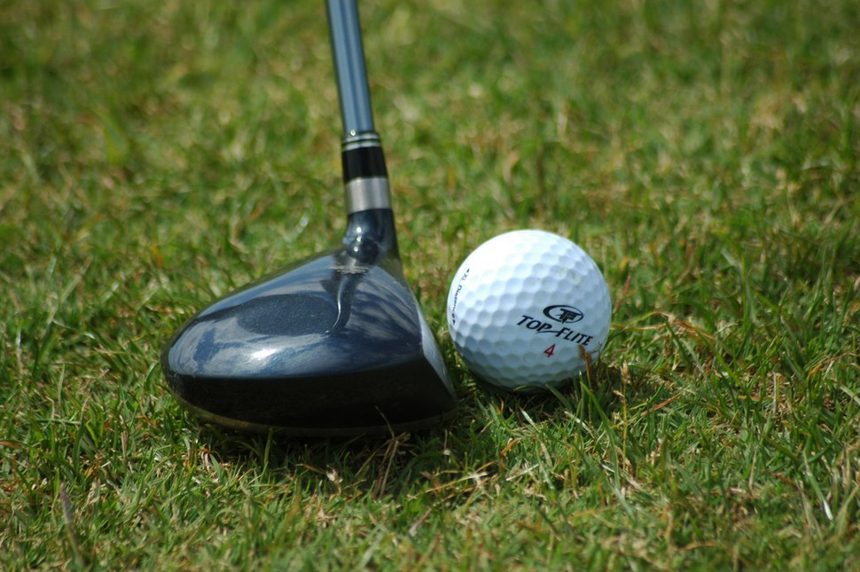 Golf ball resting near fairway wood