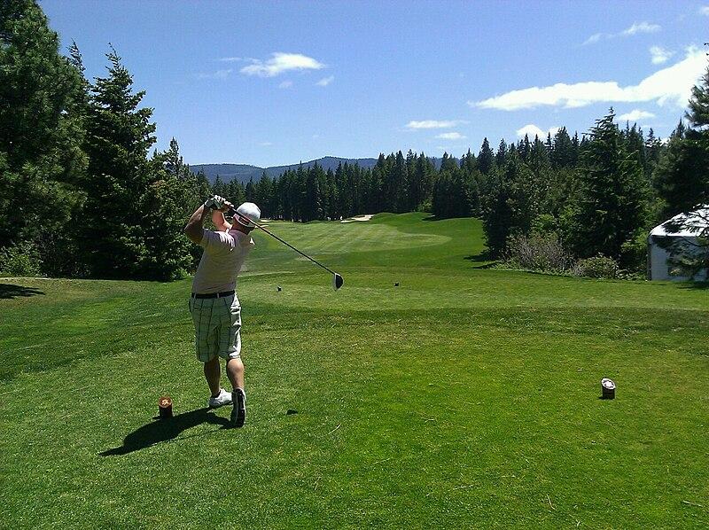 Man golfing with a rangefinder