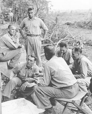 """William J. Whaling - Lt. Colonel """"Wild Bill"""" Whaling (sitting on ground) overlooking map of Guadalcanal with accompanying officers."""