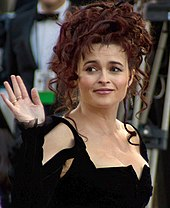 A woman with dark curly hair in a dark dress, waving