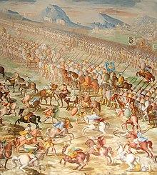 Uma pintura de uma batalha com uma longa linha de cavaleiros montados lado a lado na frente de uma linha de homens em marcha.  À frente dos cavaleiros estão vários cavaleiros lutando individualmente.
