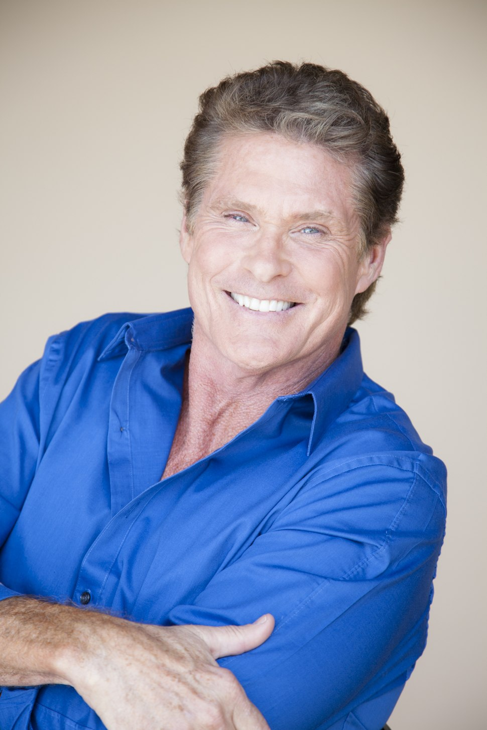 An image of Hasselhoff in a blue collared shirt smiling straight to a camera with his arms crossed