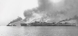 A large and obviously unfinished ship surrounded by small tugboats belching smoke.