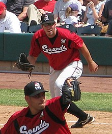 "A man with a black cap, red baseball jersey with ""Sounds"" written across the chest in white, and white pants leans forward at first base preparing to catch a ball"