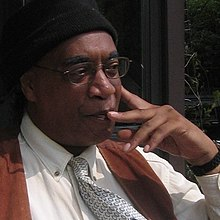 Photo of Larry Pinkney with his pointer finger resting on his cheek in deep thought.