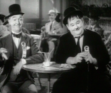 L'actor estausunidense Oliver Hardy chunto con Stan Laurel en una scena d'a cinta The Flying Deuces (1939).