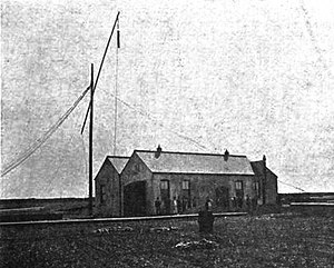 Monopole antenna - One of Marconi's early monopole antennas at his Poldhu, Cornwall transmitting station, 1900, consisting of a small metal plate suspended from a wooden arm with a long wire running down to the transmitter in the building.