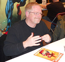 Man with black shirt and glasses, sitting at a table at a comic-book convention