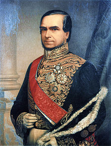 Official half-length portrait of the Marquis, who is seated with official hat in hand and wearing white gloves and a gold embroidered tunic with medals of various orders, over which is worn a red sash of office.