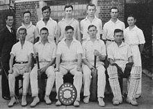 A group of 11 young cricketers in an official photo. They are wearing their white cricket uniforms, and five sit in the front row, and six stand behind them, along with a middle-aged man, their coach, in a dark suit and tie. Some are holding bats and wearing pads and a shield is bat the foot of the central boy in the front row.