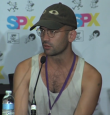 A man with round glasses, short hair, a green baseball cap with two eyes on it, and a white tank top speaks into a microphone while sitting.