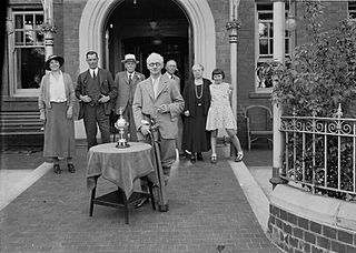Middle-aged gentleman holding golf clubs alongside a trophy, with a group of people in the background