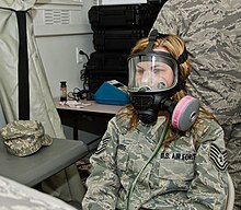 A seated woman wearing a U.S. Air Force combat uniform and a black plastic mask