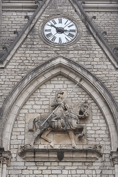 Steeple, front with knight and church clock; Montbenoît, France.