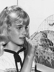 Julie Anne Haddock, age 12, with a bird in a birdcage.