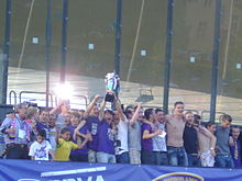 A group of individuals, some with arms round each other's shoulders, standing in a row, with two of them holding a silver trophy in the air (29 May 2011, after the match vs Domžale).