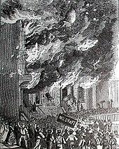 """Construyendo en llamas mientras los alborotadores miran, uno sostiene un cartel que dice """"sin corriente"""""""