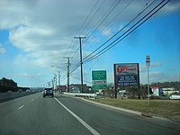 A four lane divided highway in a commercial area with a sign on the right side of the road reading Ridgedale Avenue Florham Park Parsippany upper right arrow all turns upper right arrow Morristown Airport right arrow