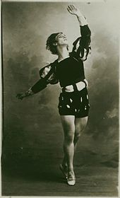 Black-and-white photograph of a costumed male dancer posed on half-toe, left arm raised upward, right arm extended backward.
