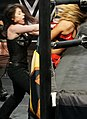 Nikki Cross repeated punches under the ring canvas on Aliyah.jpg