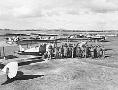 Men in flying suits with single-engined several military biplanes