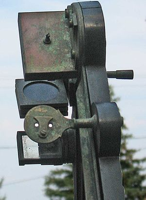 Octant (instrument) - Octant details showing the double-holed sighting pinnula.  Also visible is the small cover that can block one or the other of the holes.  The horizon mirror is on the opposite side of the instrument.  The left side is transparent while the tin amalgam on the mirrored side has completely corroded and no longer reflects light.  The back of the index mirror's holder is at the top and the three circular glass shades in square frames are between the two mirrors.
