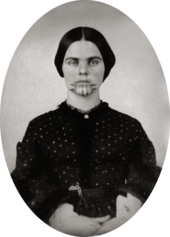 A black and white picture of a woman with a tattoo on her chin