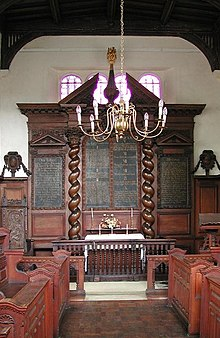 The interior of a chapel showing an elaborate wooden reredos with curling columns and inscribed panels, in front of which is a candelabrum and benches