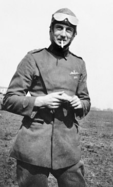 Three-quarters portrait of aviator with raised goggles in military uniform