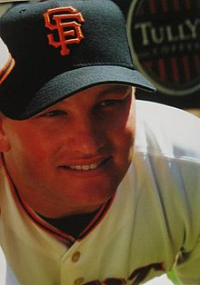 "A smiling man wearing a white baseball jersey and black baseball cap with an interlocking ""SF"" in orange on the face"