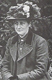 fotografia preto e branco datado de 1912 de um de meia-idade Beatrix Potter vestindo um chapéu florido virou-se ligeiramente para a direita e desviando o olhar do fotógrafo