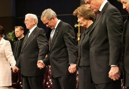 Schuller holding hands with President George W. Bush during a prayer at the homegoing celebration for Coretta Scott King at the New Birth Missionary Church in Atlanta in 2006 President George W. Bush Honors Coretta Scott King at Homegoing Celebration.jpg