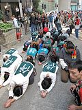 group of people prostrating in line each wearing a green top with the Chinese character for 'stop'