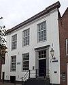 foto van Huis met gepleisterde forse lijstgevel aan de zijkanten iets naar voren springend. 19e-eeuws karakter; echter oudere opzet aanwezig