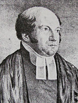 The Reverend Richard Hill is a chubbier man of middle age, with a very bald head fringed with dark curling hair. He wears parson's bands (two white tags at his neck).
