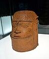cylindrisk mässingsform som representerar ett mänskligt ansikte med en flätad huvudbonad