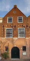foto van Pand met puntgevel, waarin geprofileerde en getoogde vensteromlijstingen en een topsieranker. In de sluitsteen van de inrijpoort met jaartal