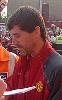 A man with dark hair and stubble, wearing a red jacket with grey sleeves.