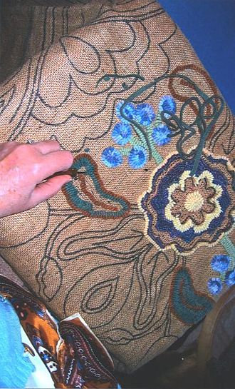 Rug hooking - A craftsperson creates a hooked rug by pulling lengths of cloth, usually wool, through a woven fabric, usually burlap.
