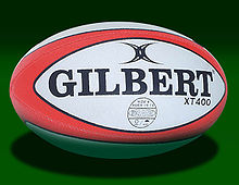 An oval shaped synthetic ball, white in colour with red trim, adorned with the manufacturers name.