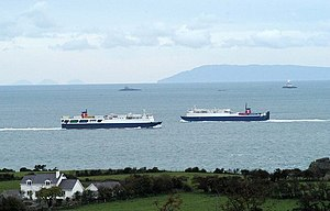 Larne - Photograph looking north from Islandmagee illustrating the proximity to Scotland.  In the foreground is Islandmagee in Northern Ireland, followed by Stena Line ferries entering and leaving Larne, and The Maidens lighthouses.  In the background are the Scottish Paps of Jura on the left and Mull of Kintyre on the right.