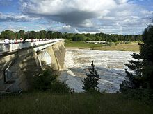 Dam wall shown with water flowing out three of the five floodgates. Spectators are gathered on the viewing area on the top of the wall watching the water flow past.