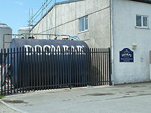 A large, cylindrical tank with the words Doom Bar written on it, lying horizontal behind the fence of an industrial unit