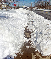 A sidewalk at the bottom of a crudely cut trench through the snow. Some snow on it is melting in the sun.