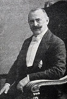Photo of Siegfried Translateur, sitting, wearing a white tie, a medal and a handlebar moustache.